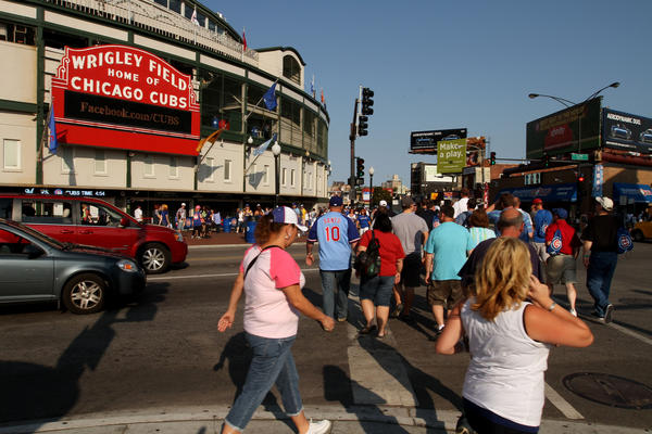 People and cars stream past Clark and Addison Streets before a Cubs game at Wrigley Field last summer.