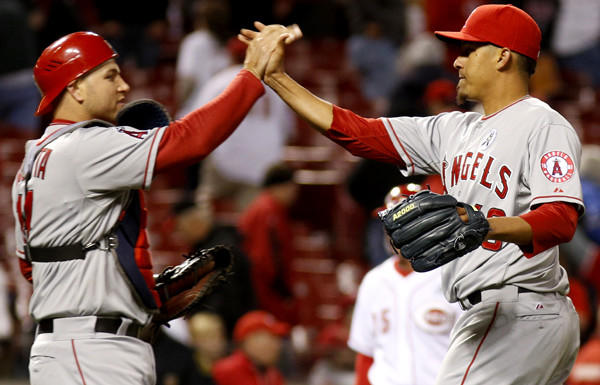 Angels catcher Chris Iannetta congratulates closer Ernesto Frieri after a 3-1 victory over the Reds in 13 innings on Monday in Cincinnati.