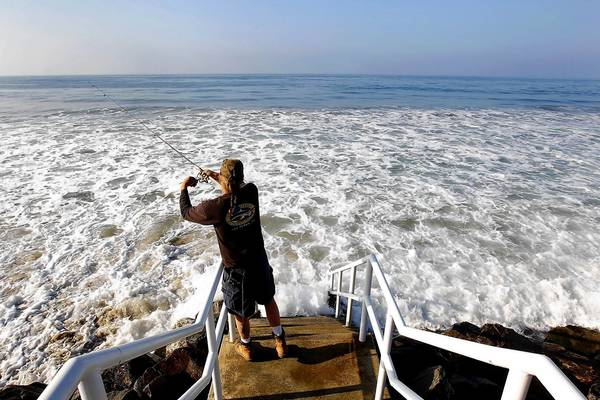 Joe Dombroski of Canoga Park fishes off public access stairs during high tide at Broad Beach in Malibu on March 24. Over several decades the beach has eroded significantly. To protect their properties, residents have piled sandbags and, more recently, built an emergency rock wall to hold back the tides.