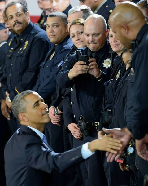 President Obama greets officers at the Denver Police Academy, where he continued his campaign calling for tighter federal gun regulations.