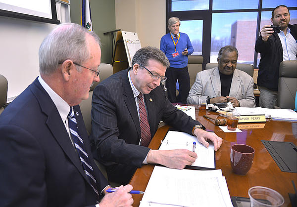 University of Charleston Regional President Jerry Forster, center, signs a transfer agreement document Wednesday as Blue Ridge CTC president Peter Checkovic awaits his turn during a ceremony at Blue Ridge campus in Martinsburg, W.Va.