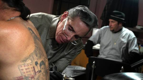 Tattoo artist Mark Mahoney works on Danny Trejos