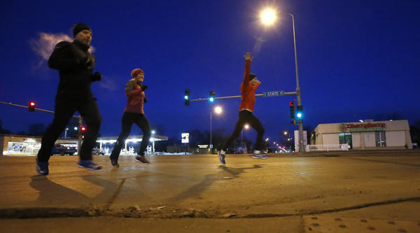 Kevin Bjerke, right, celebrates the completion of a morning run as he and Sonya Nilsson, center and Dave Derzab, left, cross Sixth Avenue Southeast along South State Street Tuesday morning at approximately 6:40 a.m. American News Photo by John Davis