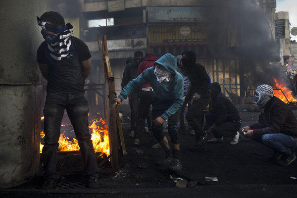 Palestinians clash with Israeli forces in the West Bank city of Hebron.