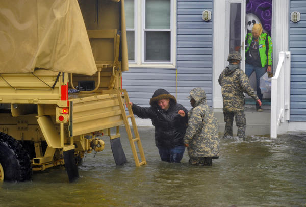 A military truck sits in the water on St. Louis Avenue between 8th and 9th Streets as personnel help residents (two women, one man and family pet) evacuate with their essential belongings from their apartment as Hurricane Sandy floods Ocean City.