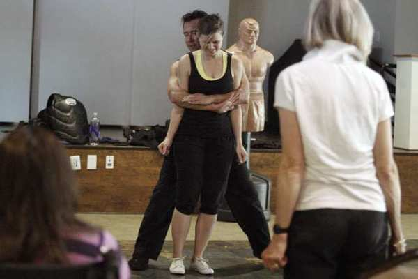 Women's self defense instructor Nelson Nio, left, tries to teach Vivian Geiseler some moves during a self defense class.