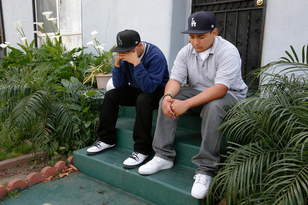 Ruben Fernandez, 15, left, and his brother Anthony, 18, mourn the loss of their father Leonardo Fernandez on the front steps of his home in East Los Angeles.