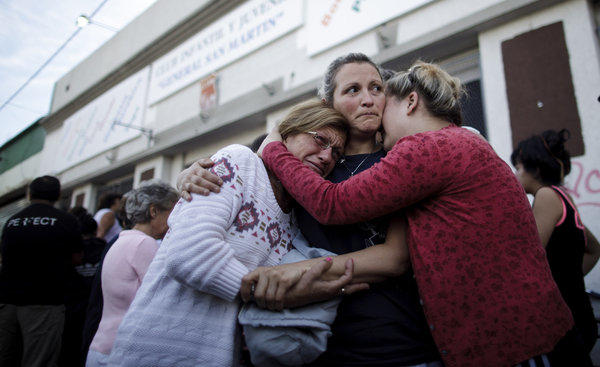 People embrace outside a club where the Red Cross set up a center to help flood victims in La Plata, Argentina, on Thursday.