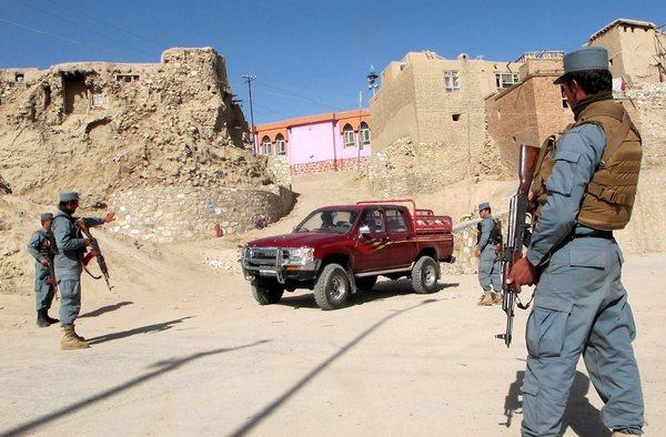 Afghan policemen check a vehicle on a roadside in Ghazni province, Afghanistan, on Thursday.