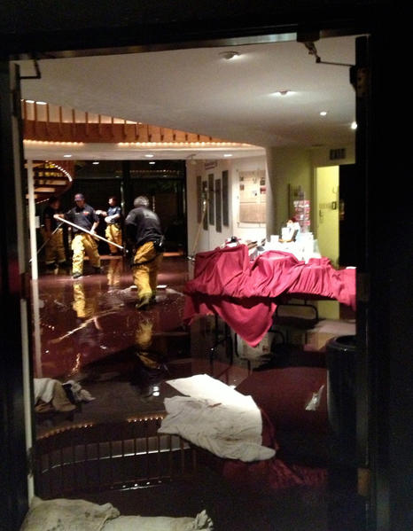 Laguna Beach firefighters clean up the scene at the Laguna Playhouse after a pipe burst and flooded the lobby.