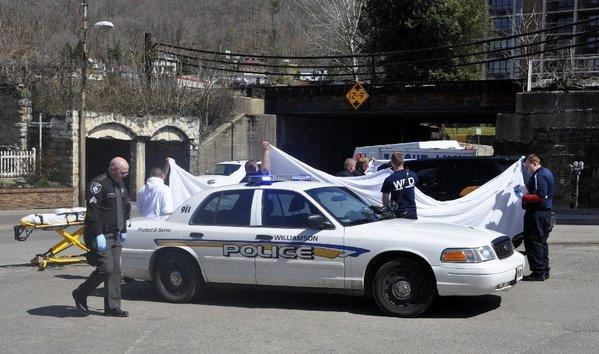 Law enforcement officers and emergency service personnel cover the vehicle at the scene of the shooting in downtown Williamson, W.Va., Wednesday, April 3, 2013, where Sheriff Eugene Crum was shot and killed.