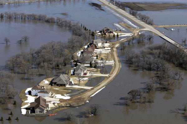 The flooded Red River surrounds houses near Fargo, N.D., in 2010. Scientists say climate change will produce more intense storms, increasing the risk of damaging floods.