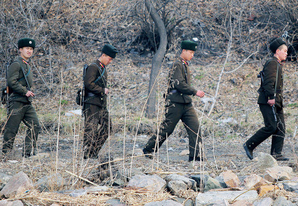 North Korean soldiers patrol along the bank of the Yalu River in the North Korean town of Sinuiju, across from the Chinese city of Dandong, on April 4, 2013.