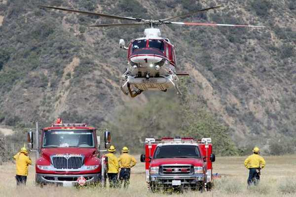 An OCFA helicopter lands after dropping search and rescue members into areas that have not been already searched in Trabuco Canyon on Tuesday.