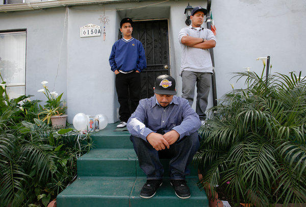 Three sons mourn the loss of their father Leonardo Fernandez on the front steps of his home in East Los Angeles on April 1.