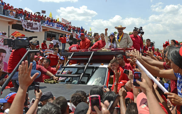 Venezuelan acting President Nicolas Maduro (center at right, with hat) and his wife Cilia Flores greet supporters during a campaign rally in San Carlos.