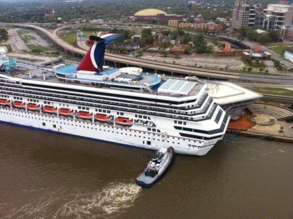 A tug pushes the Carnival Triumph to a mooring at the Signal International shipyard in the Mobile, Ala.