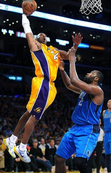 Lakers guard Kobe Bryant goes baseline for a dunk over Dallas Mavericks forward Elton Brand.