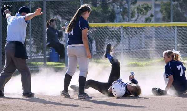 Burbank High's Kaitlin Brooks, center, is called safe at third base during a 9-1 win at Crescenta Valley.