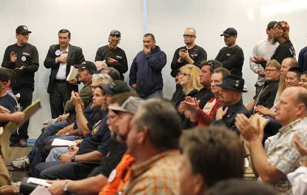 Members of a local construction union stand in support as they and others filled the Coast Community College District board meeting to listen to comments on how to spend millions of Measure M grant money Wednesday.