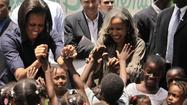 Michelle Obama (L) and Elisabeth Debrosse, wife of Haitian President Rene Preval, greet children during her visit to a local child welfare project in Port-au-Prince April 13, 2010.
