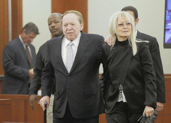 Las Vegas Sands Corp. Chief Executive Sheldon Adelson walks into court with his wife, Miriam, as he prepares to testify in a breach-of-contract case involving his company.