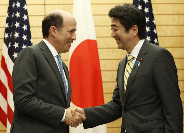 Japanese Prime Minister Shinzo Abe, right, shakes hands with U.S. Ambassador to Japan John Roos in Tokyo on Friday at their joint announcement of the Okinawa plan.