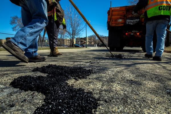 A crew from the Chicago Department of Transportation fills potholes along 44th Street at State Street.