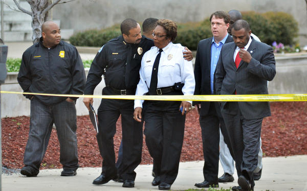 Jackson, Miss., Assistant Police Chief Lee Vance, center left, comforts Chief Rebecca Coleman, center right, after the slaying of a detective.