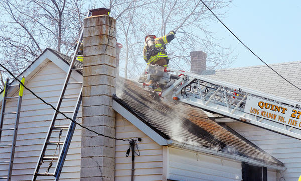 A firefighter cuts a hole in the roof for ventilation at a home on Cavetown Church Road after a fire damaged the two story home Friday afternoon.