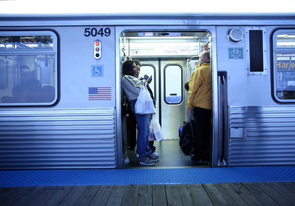 Riders standing in a CTA train entryway