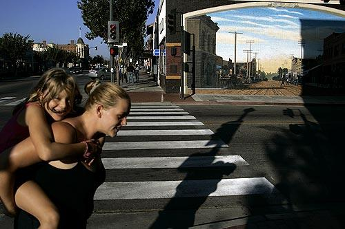 Andrea Merritt, who has no role in the housing dispute, carries her daughter, Cara, 7, at Mill and Main streets in Santa Paula.