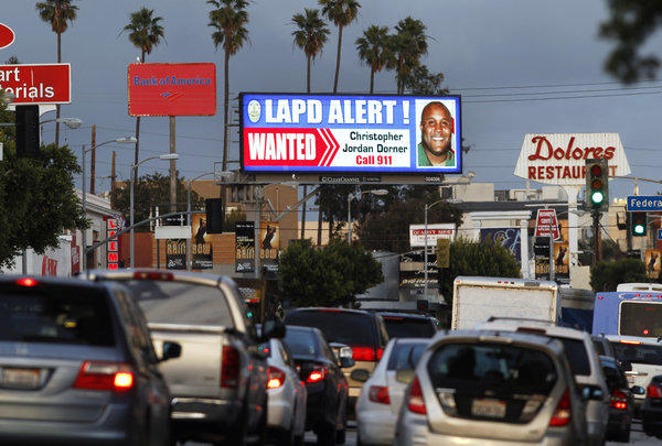 "A digital billboard along Santa Monica Boulevard on the west side of Los Angeles shows a ""wanted"" alert for former Los Angeles police officer Christopher Dorner."