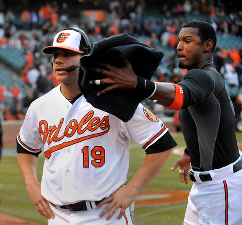 Adam Jones races around Chris Davis to give him a postgame pie to the face during a TV interview.