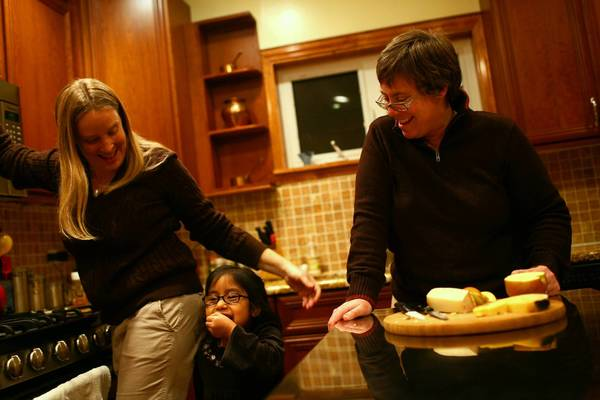Lesbian parents RoiAnn Phillips, left, and Kelly Fondow make an after-school snack for their daughter, Eva, 5.