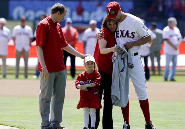 From left, Robbie Parker, daughter Samantha, wife Alissa and Texas Rangers' David Murphy gather on the field before Robbie threw out the ceremonial first pitch.