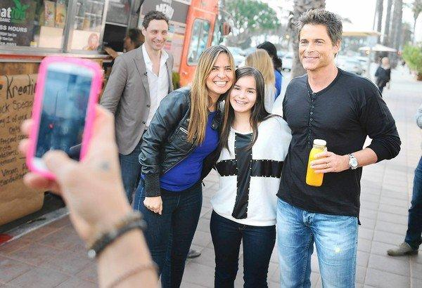 Rob Lowe, right, poses for pictures with tourists outside 41 Ocean, a members-only club in Santa Monica.
