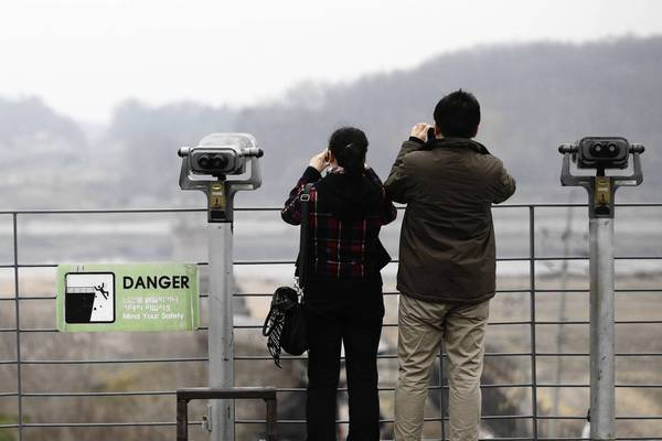Tourists in South Korea point their cameras toward the village of Panmunjom, which sits on the border with North Korea.