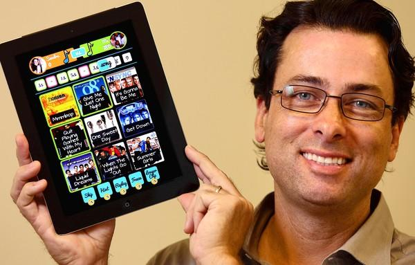 Company co-founder Greg Sukornyk holds his iPad with the latest game up on it.