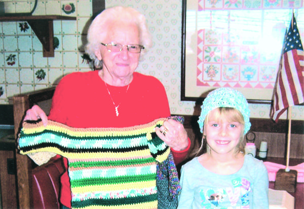 Ruth Paul of Hillcrest Grange displays one of a number of patterns of crocheted sweaters that she has created for community service projects using yarn that was given to her from the Harold Lambert estate. Ashley Brant of Hillcrests Junior Grange is wearing one of Ruths crocheted hats.
