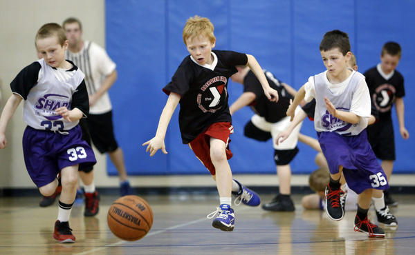 Jayden Frohling, of Groton, center, pushes the ball up the floor between Andrew Czeck, left and Reese Stark, right, of Watertown Sharp's 2 during their bracket 3-2 game Friday at the Aberdeen Family YMCA 2013 Boys Interstate Y Basketball Tournament. photo by john davis taken 4/5/2013