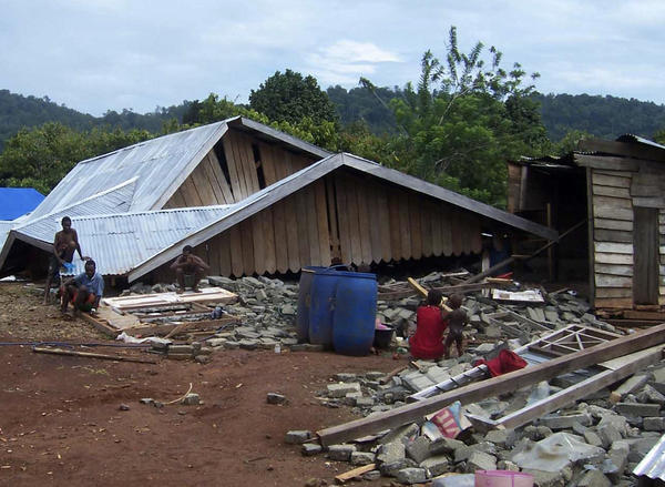 Residents sit outside of their damaged houses after an earthquake hit West Papua in January 2009.