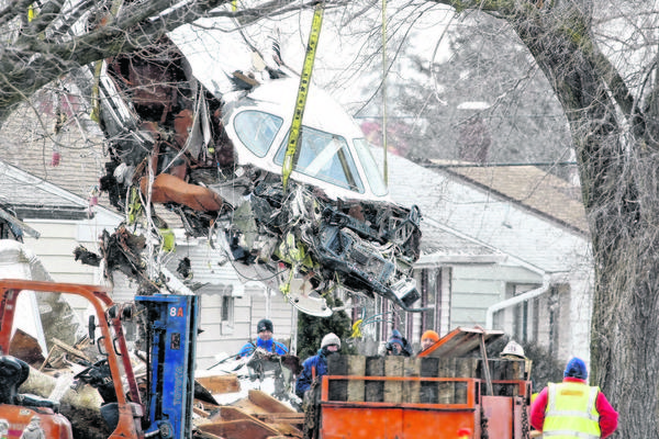 A portion of a jet is lifted by a crane before being put on a flatbed truck on March 19. The jet, which crashed March 17, was taken to a hangar at South Bend Regional Airport for further investigation.