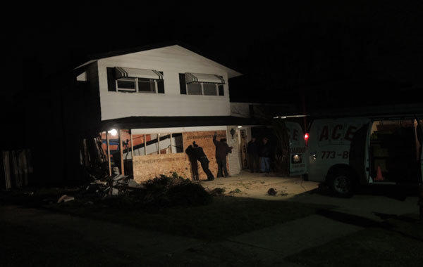Workers board up the front of an Oak Lawn home damaged in a crash Friday night.