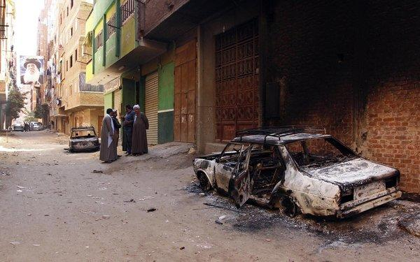 Several burned cars belonging to Egyptian Christians remain in the street after clashes between Muslims and Christians just outside Cairo on Saturday. A picture of the late Coptic Pope Shenouda is seen at end of street.