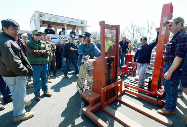 Auction goers bid on several hydraulic lifts Friday afternoon at Cochran Auctions in Boonsboro.