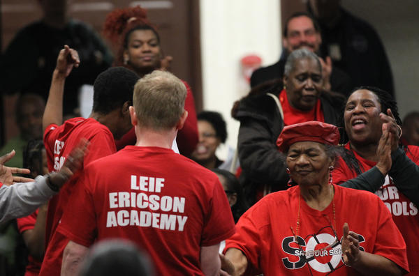 Ericson Elementary parents cheer math teacher Michael Colwell, center, after he questioned why CPS is closing their school, when they have better test scores than many other schools that are not in the list, during a hearing on school closings held at Manley High School.