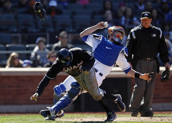 Miami Marlins' Juan Pierre scores on a hit by Greg Dobbs in front of New York Mets catcher John Buck during the seventh inning of their MLB National League baseball game at CitiField in New York, April 6, 2013. Pierre was called for interference resulting in Dobbs being called out at first base. REUTERS/Adam Hunger (UNITED STATES - Tags: SPORT BASEBALL) ORG XMIT: NYM10