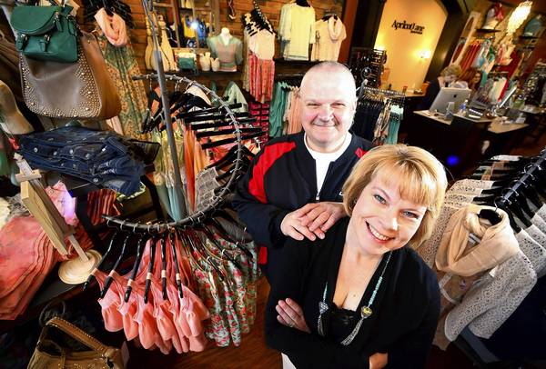 Jeff and Susan Kittle, co-owners of Apricot Lane Boutique in the Promenade Shops at Saucon Valley, show off garments in their new store.