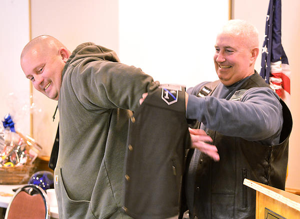 New Maryland chapter president Scott Leeney, right, slips a new leather vest onto new member Brad Creek. The Defenders Law Enforcement Motorcycle Club held an opening ceremony for the new chapter of riders made up of mostly law enforcement workers.